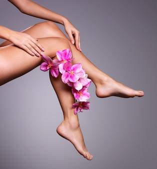 Mooie lange vrouwelijke benen met bloem. schoonheidsbehandeling concept