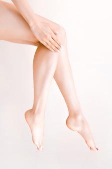 Mooie lange vrouwelijke benen met gladde huid na ontharing op een pastelbeige achtergrond