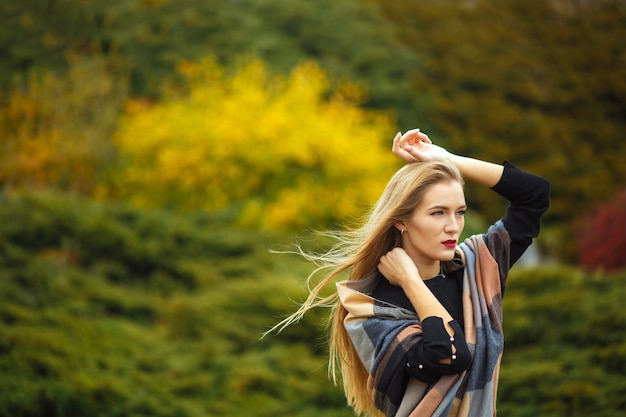 Mooie langharige blonde meid met sjaal, poseren in de botanische tuin. ruimte voor tekst