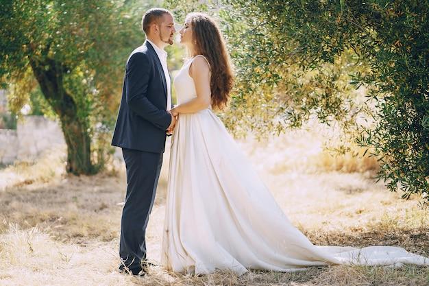 Mooie langharige bruid in witte jurk met haar jonge man lopen in de natuur