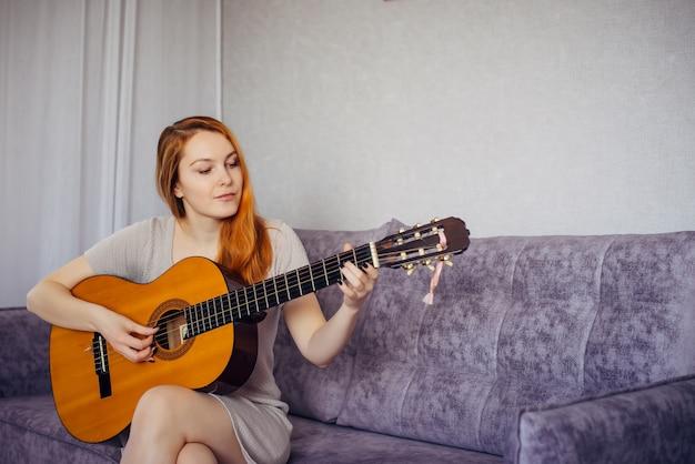 Mooie langharige jonge vrouw met een positieve geestelijke gezondheid die lacht, haar favoriete liedje speelt op akoestische gitaar, thuis op de bank zit. muzikale hobby, vrije tijd.