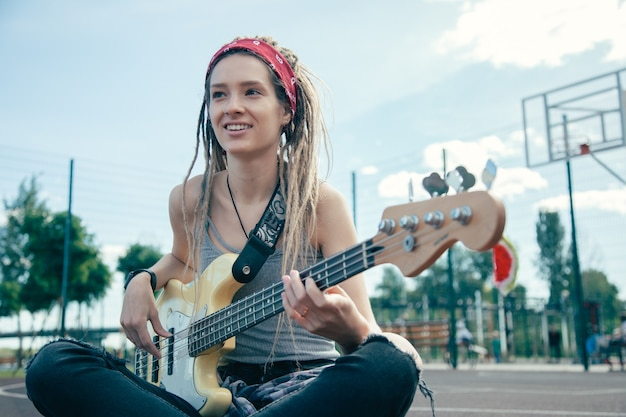 Mooie langharige jonge vrouw zittend op de grond en lachend terwijl u geniet van het spelen van de gitaar