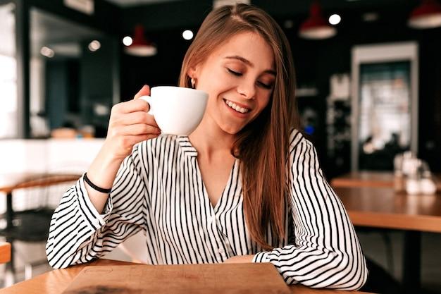 Mooie langharige meisje zit in het café met koffie en kijkt verlegen weg