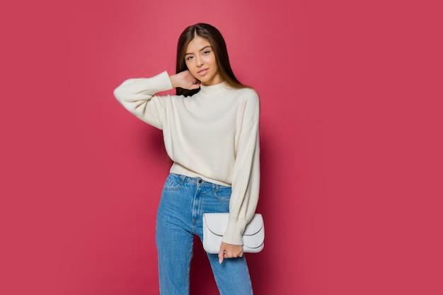 Mooie langharige vrouw in gezellige witte pullover en casual jeans poseren op roze achtergrond isoleren. holding eco lederen handtas.