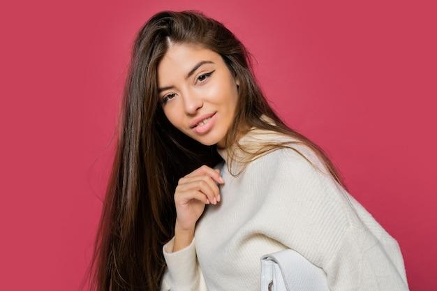 Mooie langharige vrouw in gezellige witte trui en casual jeans die zich voordeed op roze.