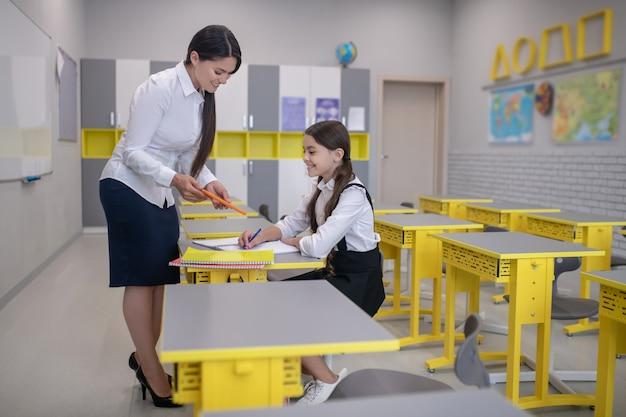 Mooie langharige vrouw op hoge hakken tablet tonen aan vrolijke schoolmeisje zit in de klas aan haar bureau