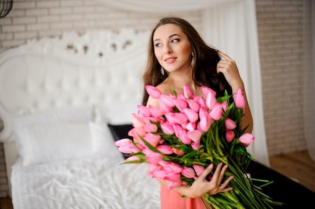 Mooie langharige vrouw zittend op het bed met boeket tulpen