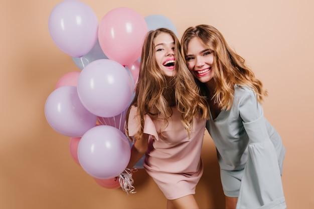 Mooie langharige vrouwen die bij verjaardagsfeestje een grapje maken