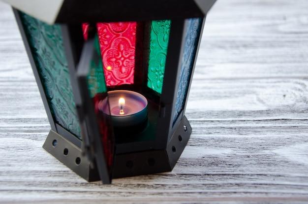 Mooie lantaarn met een kaars die binnen op een grijze houten achtergrond, selectieve nadruk op de kaars branden