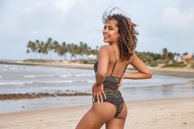 Mooie latijns-amerikaanse vrouw in bikini op het strand. jonge vrouw geniet van haar zomervakantie op een zonnige dag, glimlachend en kijkend naar de camera