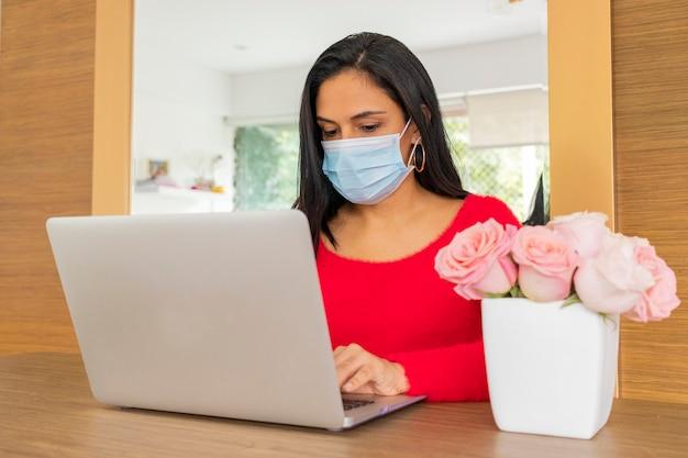 Mooie latijnse vrouw die thuiskantoor leidt voor de coronavirus pandemie