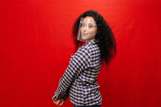 Mooie latijnse vrouw met afrohaar en polyvinylchloride - pvc-gezichtsscherm, coronaviruspreventie