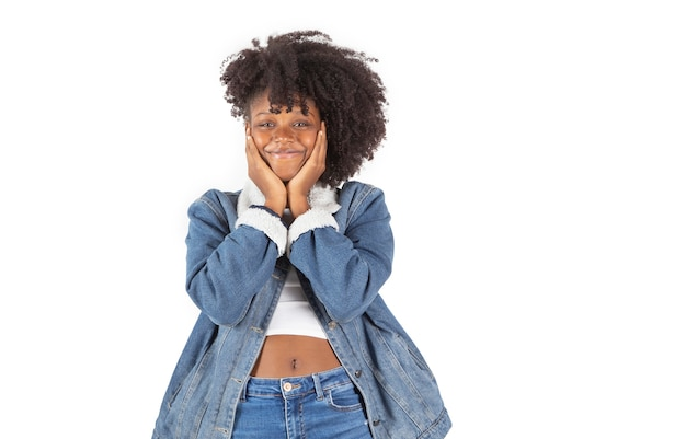 Mooie latijnse vrouw met afrohaar, het dragen van denimkleren, handen op gezicht witte achtergrond