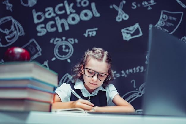 Mooie leerling zit aan bureau en studeert online met laptop tegen zwarte achtergrond