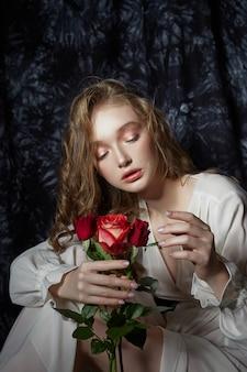 Mooie lente meisje zit op de vloer met roze bloemen in haar handen. vrouw in een witte jurk droomt, een romantisch beeld. blond met krullend haar