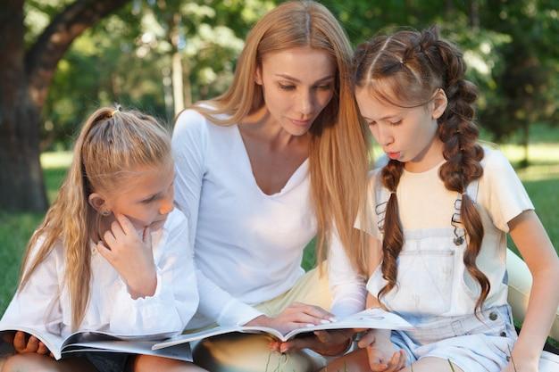 Mooie leraar en haar vrouwelijke leerlingen die samen in het park lezen