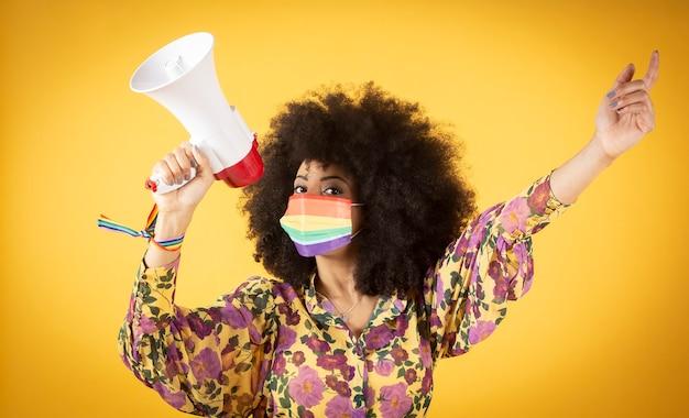 Mooie lesbische afro-amerikaanse vrouw met lgbt-regenboogvlag