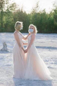 Mooie lesbische paar wandelen op zand langs een rivieroever op hun trouwdag