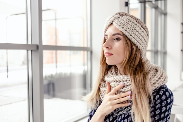 Mooie leuke vrouw gebreide muts en sjaal dragen op café achtergrond.