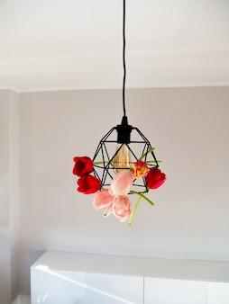 Mooie levendige tulpen in geometrische lamp en gloeilamp van edison op witte achtergrond.