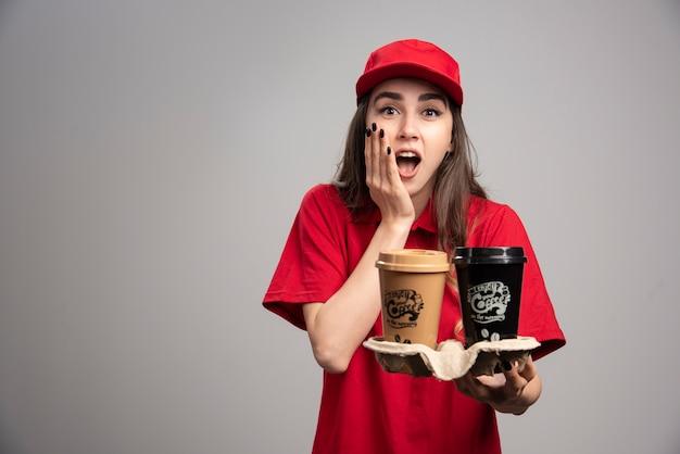 Mooie leveringsvrouw die haar gezicht en koffiekopjes houdt.