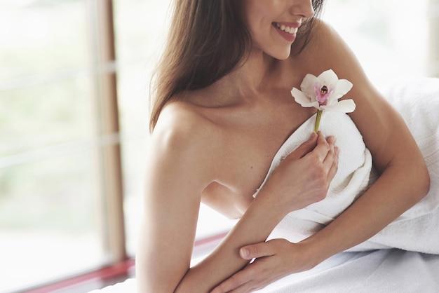 Mooie lichaamsvrouw met witte bloemorchidee en lichaamsverzorging.