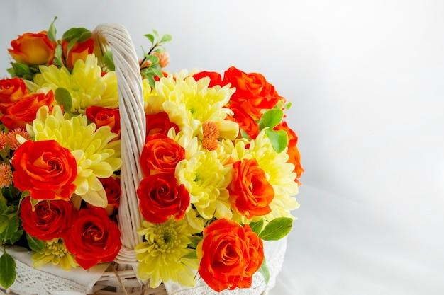 Mooie lichte rieten mand met gele en rode bloemen vakantie lente gefeliciteerd