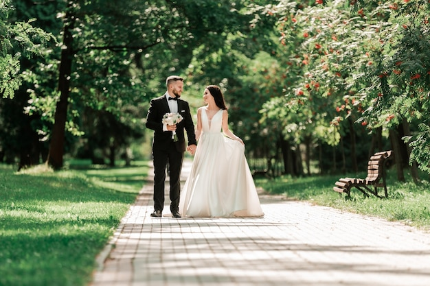 Mooie liefdevolle paar wandelen langs het pad in het stadspark. evenementen en tradities