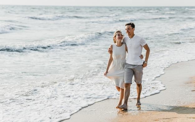 Mooie liefdevolle paar wandelingen aan de kust. gelukkig jong stel brengt tijd door op het strand. huwelijksreis pasgetrouwden. man met meisje bij het aanbreken van de dag. stel op vakantie. zomerrust. paar knuffelen