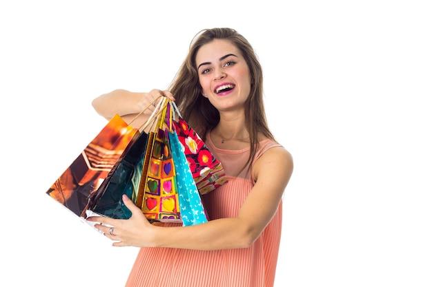 Mooie lieve meid houdt pakjes met aankopen in de hand en lacht