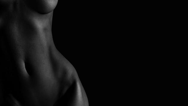 Mooie lijnen van het vrouwelijk lichaam op een donkere achtergrond