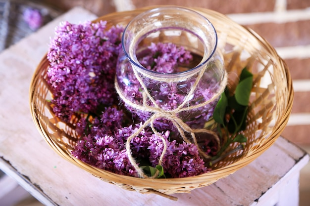 Mooie lila bloemen in vaas, op houten ladder, op kleur muur achtergrond