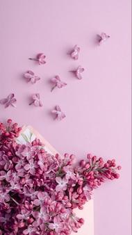 Mooie lila bloemen op envelop op een achtergrond met dezelfde kleur. minimalistische trendy bloemensamenstelling.