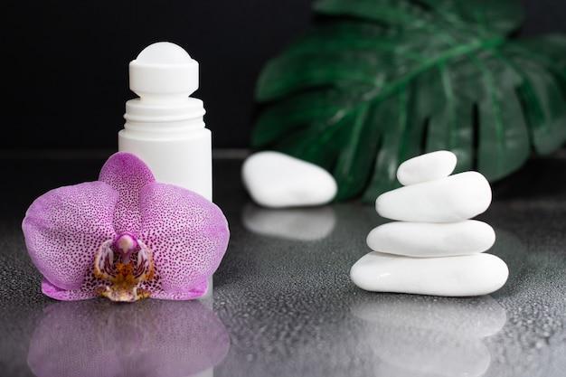 Mooie lila orchideebloem en witte roll-on deodorant met witte stenen en monsterabladeren, op zwarte natte achtergrond
