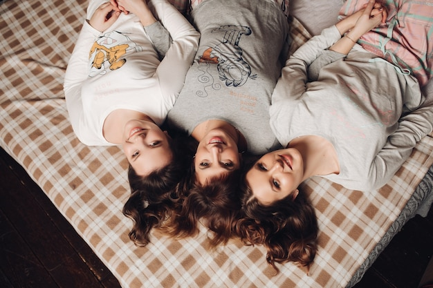 Mooie lookalike dochters en moeder ontspannen op het bed met een geruite deken
