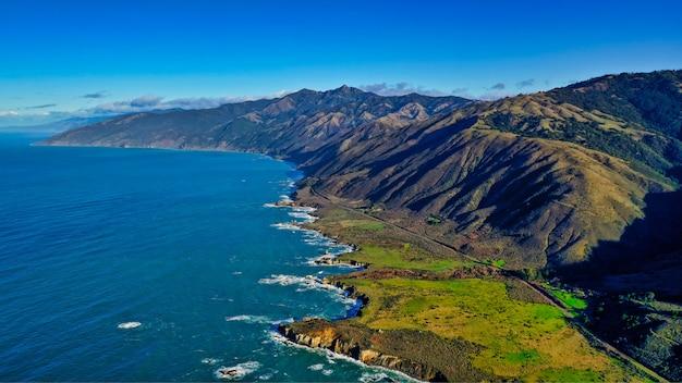 Mooie luchtfoto van de kust van de zee met groene bladeren en bewolkte verbazingwekkende hemel