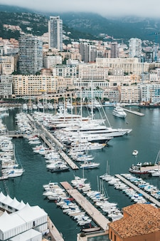 Mooie luchtfoto van een dok met veel geparkeerde schepen en een stedelijke stad op de achtergrond
