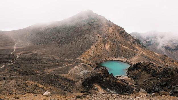 Mooie luchtfoto van een klein meertje in het midden van de woestijn in de buurt van een berg op een mistige dag