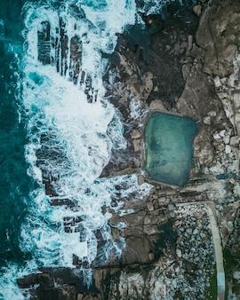 Mooie luchtfoto van rotsachtige kust en oceaan golven