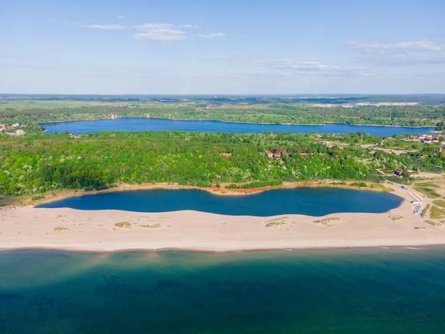 Mooie luchtfoto van zandstrand, meer aan de zeekust en bos gemaakt met drone aan de baltische zee, yantarny, rusland