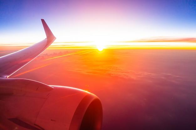 Mooie luchtmening van vliegtuigvleugel op witte wolk en hemel in zonsondergangtijd