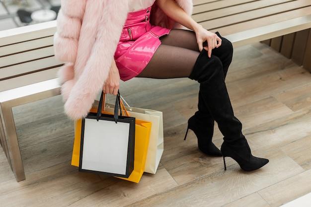 Mooie luxe jonge vrouw in chique modieuze kleding met tassen