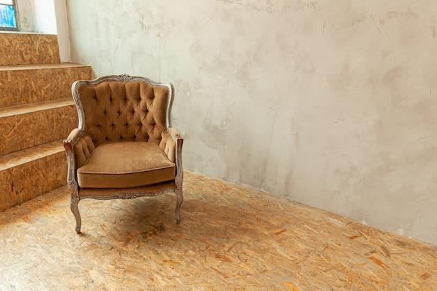 Mooie luxe klassieke biege schone binnenruimte in grungestijl met bruine barokke fauteuil.
