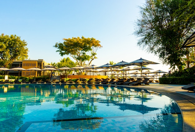 Mooie luxe paraplu en stoel rond buitenzwembad in hotel en resort met blauwe hemel