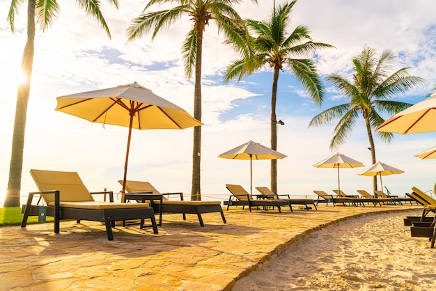 Mooie luxe paraplu en stoel rond buitenzwembad in hotel en resort met kokospalm boom op zonsondergang of zonsopgang hemel