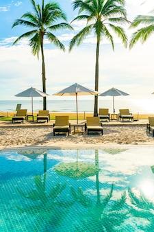 Mooie luxe parasol en stoel rond buitenzwembad in hotel en resort met kokos palmboom op blauwe lucht, vakantie en vakantie concept