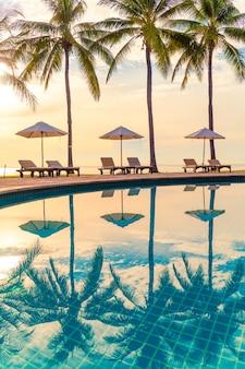 Mooie luxe parasol en stoel rond buitenzwembad in hotel en resort met kokos palmboom op zonsondergang of zonsopgang hemel - concept vakantie en vakantie