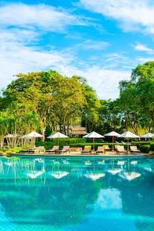 Mooie luxe parasol en stoel rondom buitenzwembad in hotel en resort