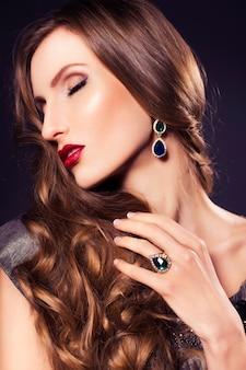 Mooie luxe vrouw in jurk met heldere huid en donkere avond make-up: groen kattenoog en bruine oogschaduw. golvend kapsel. donkere achtergrond