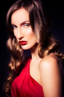 Mooie luxe vrouw in rode jurk met heldere huid en donkere avond make-up: groen kattenoog en bruine oogschaduw. golvend kapsel. donkere achtergrond